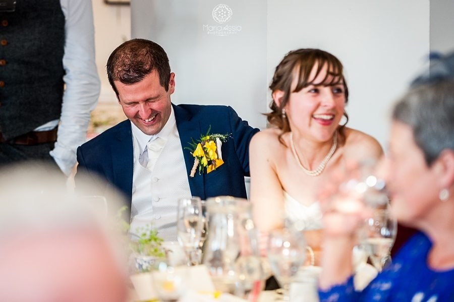 Bride and Groom laughing at their wedding speeches at the Sir Christopher Wren Hotel