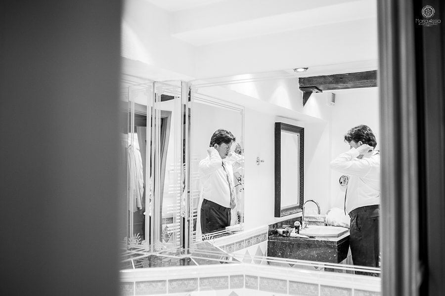 Groom getting ready reflecting in a mirror