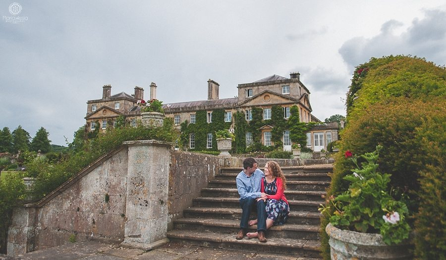 Engaged couple sitting at Bowood House stairs