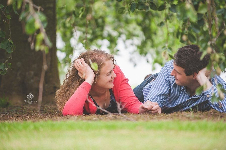Engaged couple lying under a tree