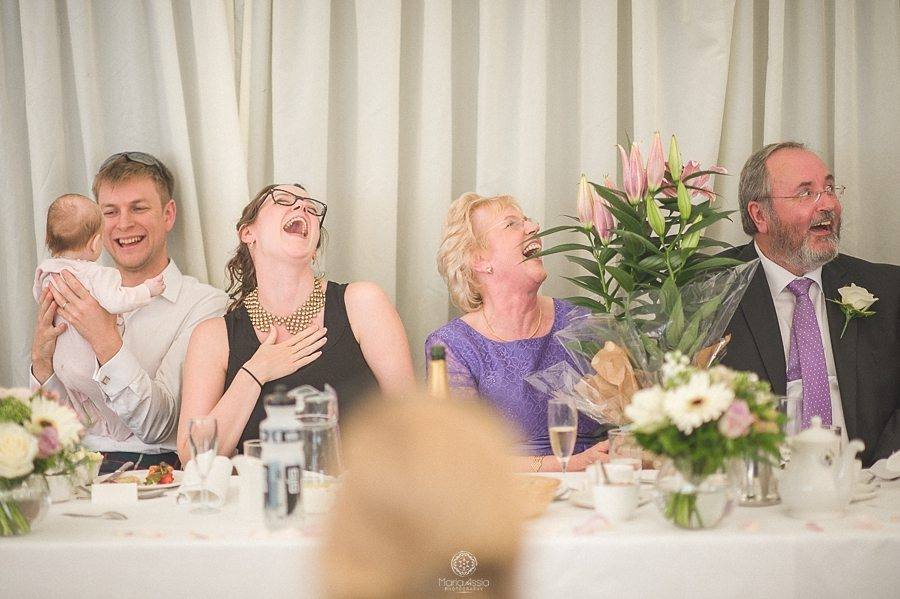 Guests laughing at wedding speeches at Birtsmorton Court Navy Blue Wedding - Maria Assia Photography