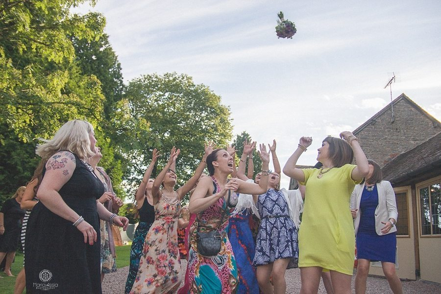 Girls catching the bride's flowers at a Birtsmorton Court Navy Blue Wedding - Maria Assia Photography