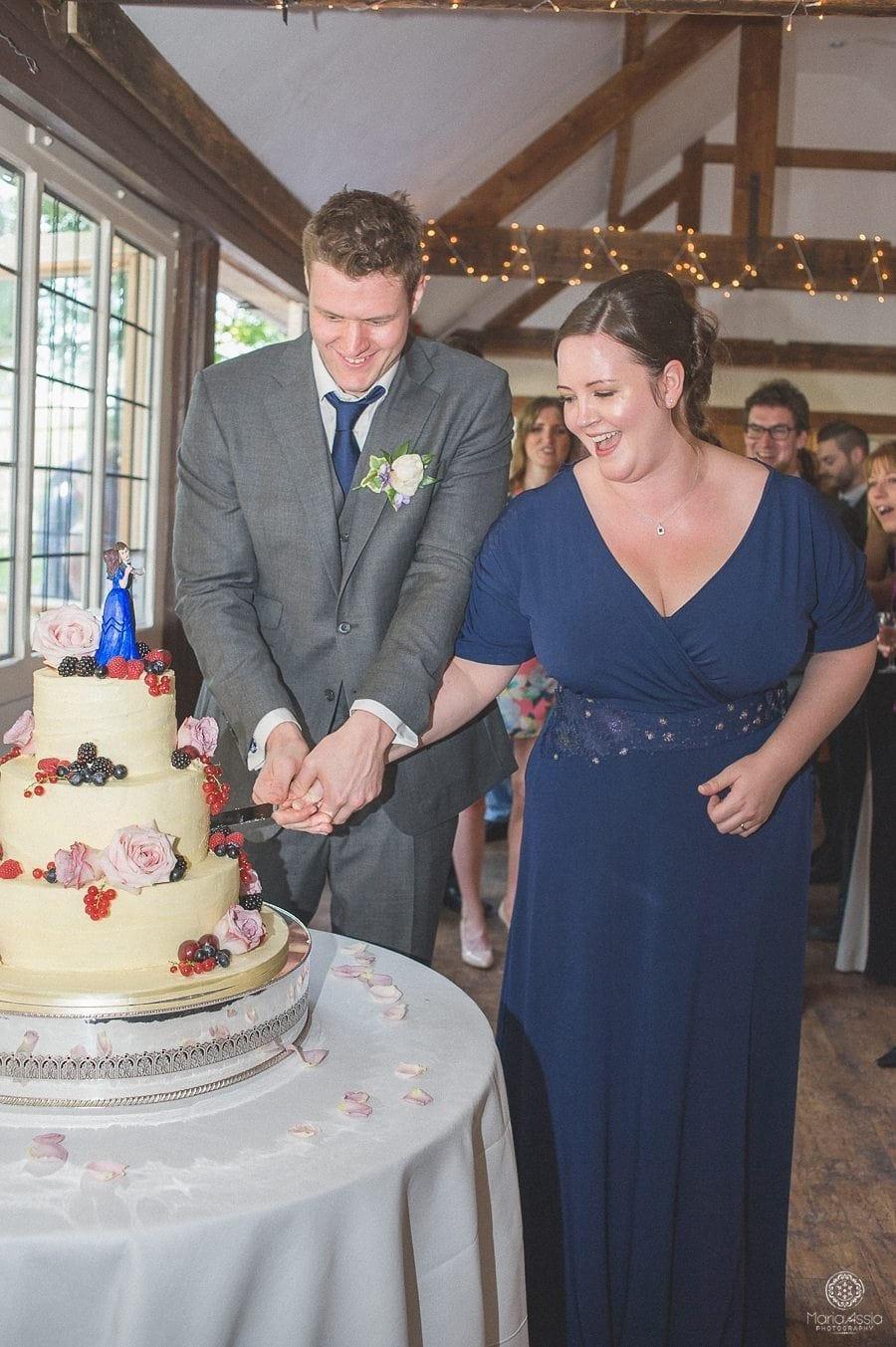 bride and groom cutting the wedding cake at their Birtsmorton Court Navy Blue Wedding - Maria Assia Photography