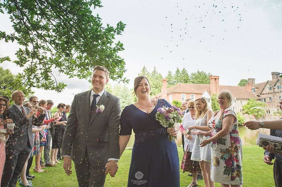 Bride and Groom walking through confetti at Birtsmorton Court