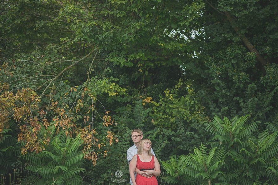 Engaged couple leaning on each other surrounded by luscious greenery