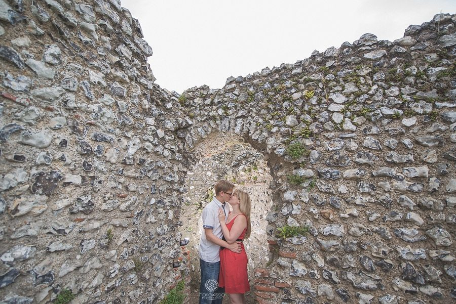 Engaged couple kissing surrounded by the flint ruins of Eynsford Castle