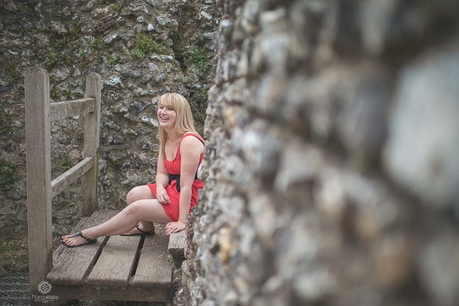 Girl in a red dress sitting and laughing at Eynsford Castle