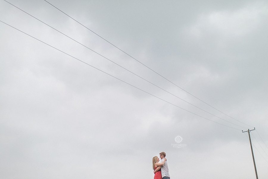 Couple framed by power lines and a cloudy sky