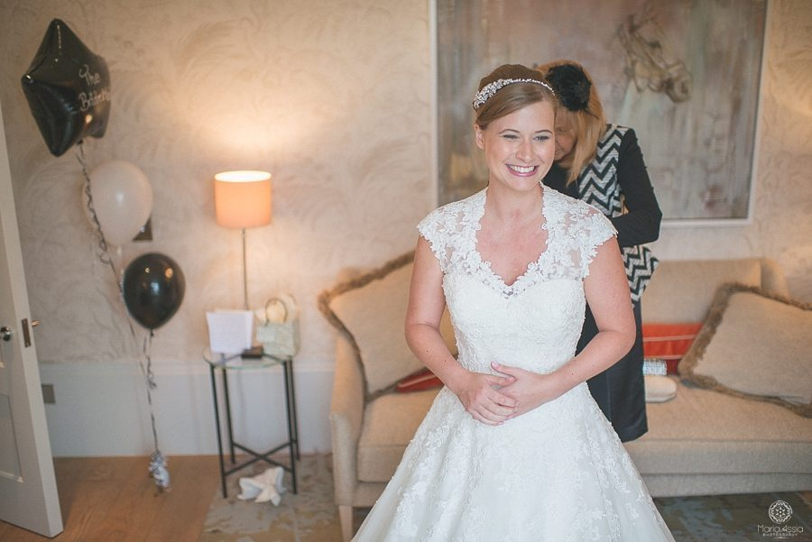 Happy Bride getting into her wedding dress in the bridal suite at Coworth Park