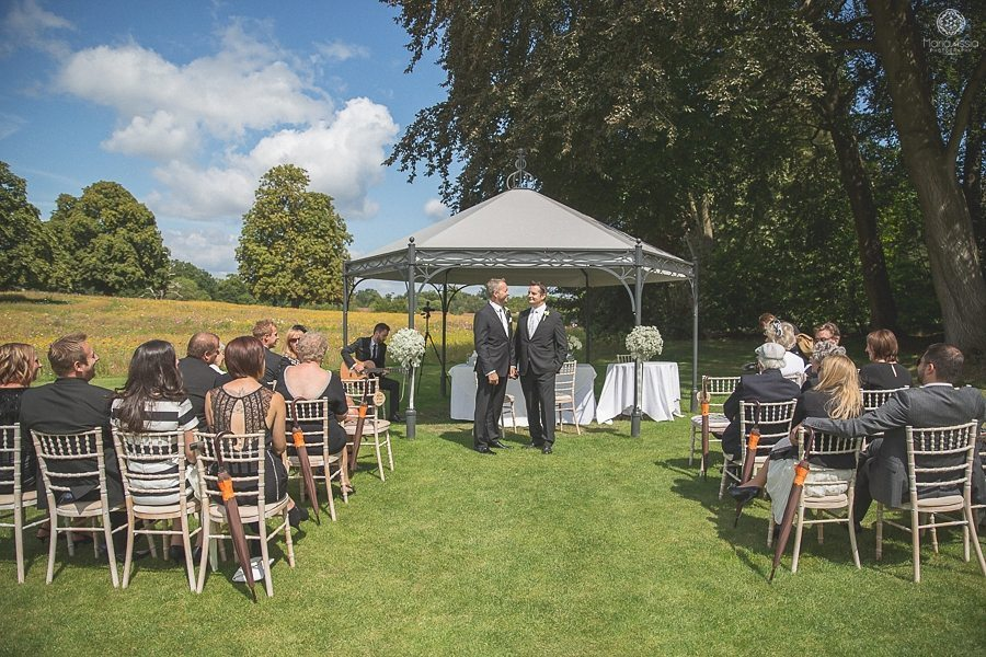 Groom talking to his best man and guests in the meadow at Coworth Park summer wedding