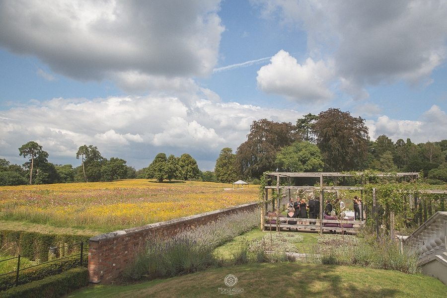A Photo Overlooking the wild flower meadow at a summer wedding at Coworth Park