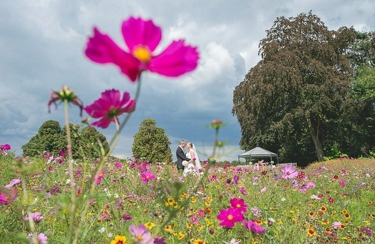 Bride and groom standing in the Coworth Park meadow