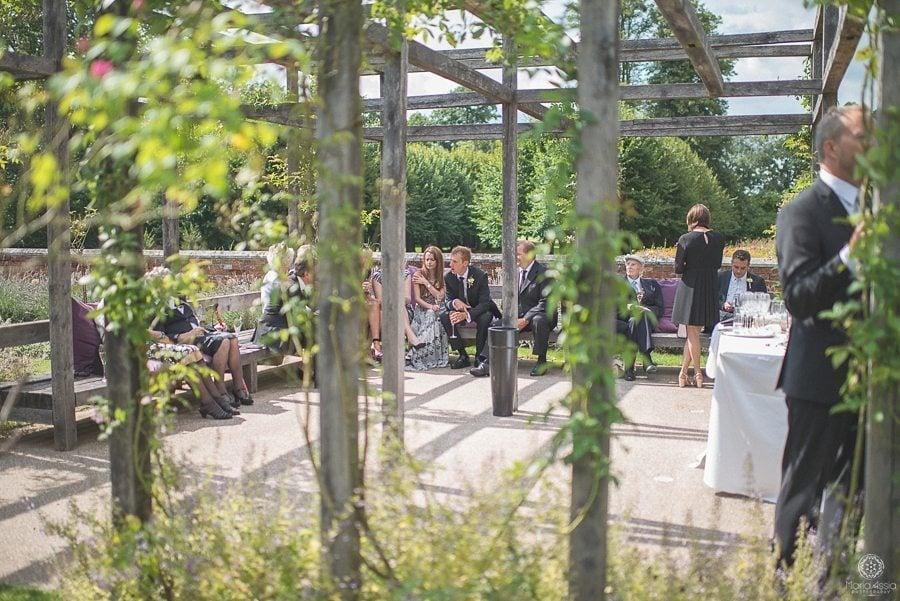 Wedding guests chatting in the sunken garden at Coworth Park