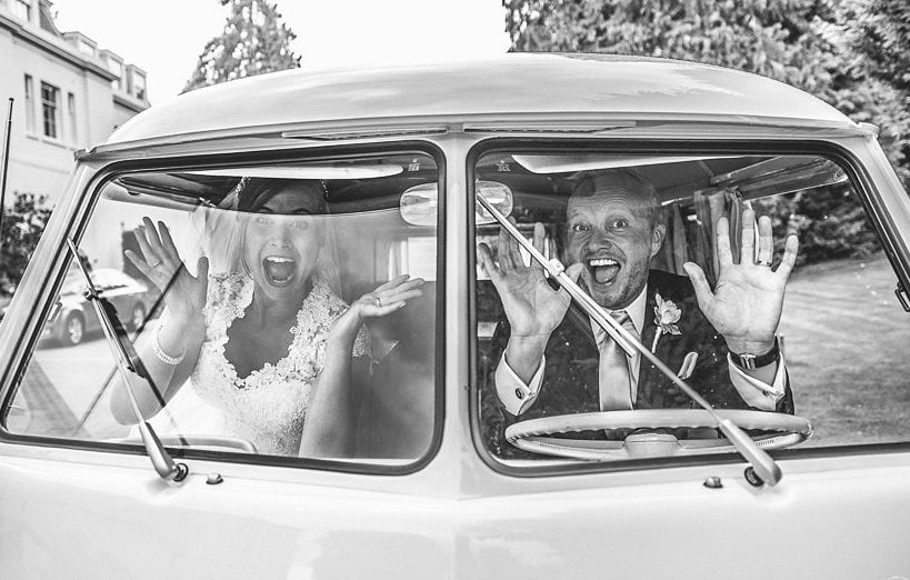 Bride and groom pulling faces in a white VW van in front of Coworth Park