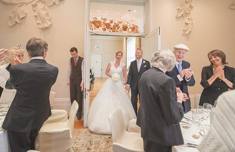 Guests cheer as the Bride and groom enter the Oak Room at Coworth Park