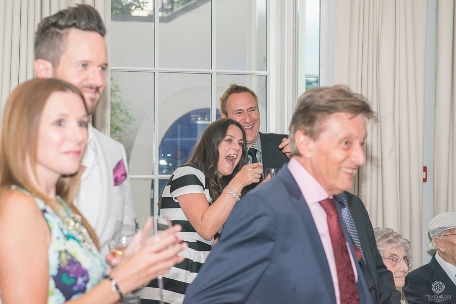 Wedding guests laughing at father's speech