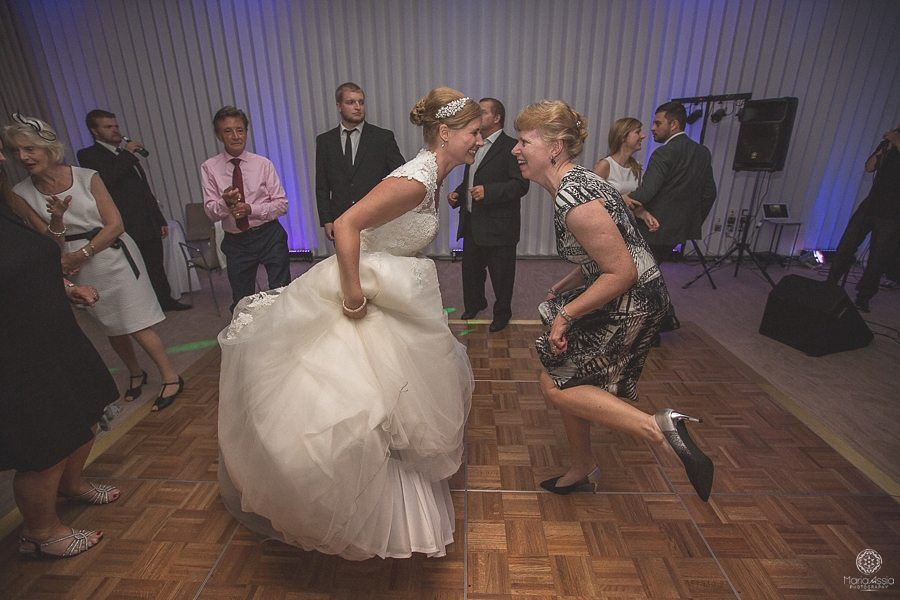 Bride kicking her legs out as she dances with her aunt