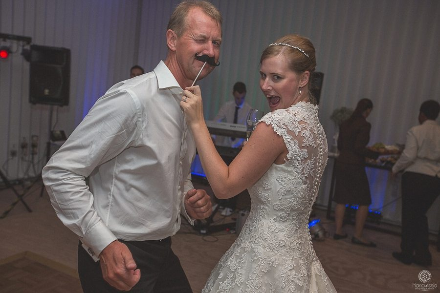 Bride dances with her father and holds up a fake moustache