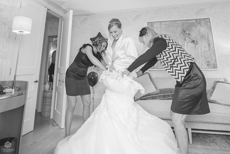 Black and white photo of bride climbing into her dress