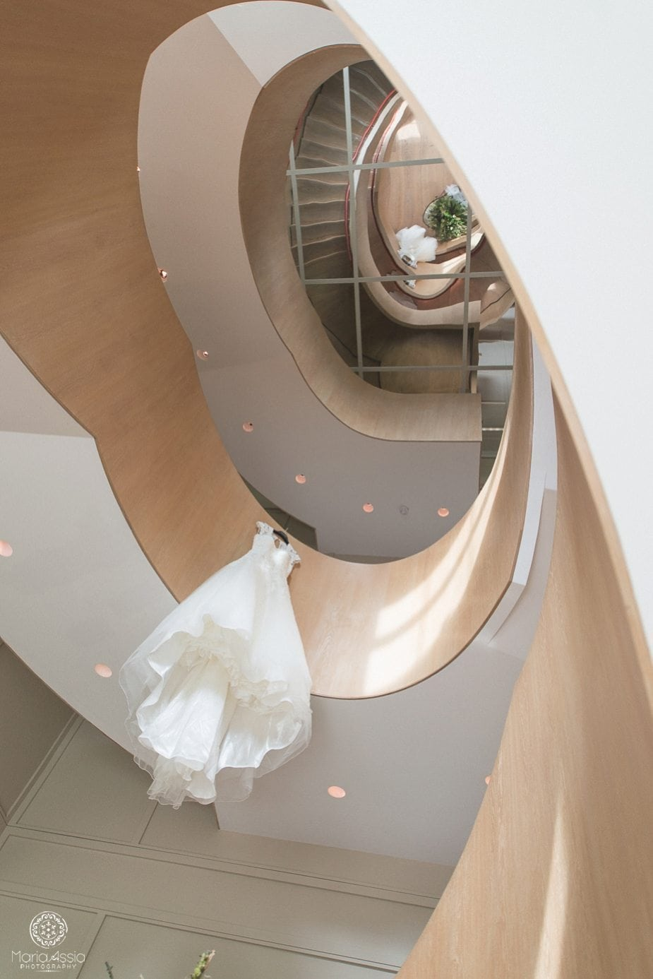 Wedding dress hanging from the spiral staircase at Coworth Park