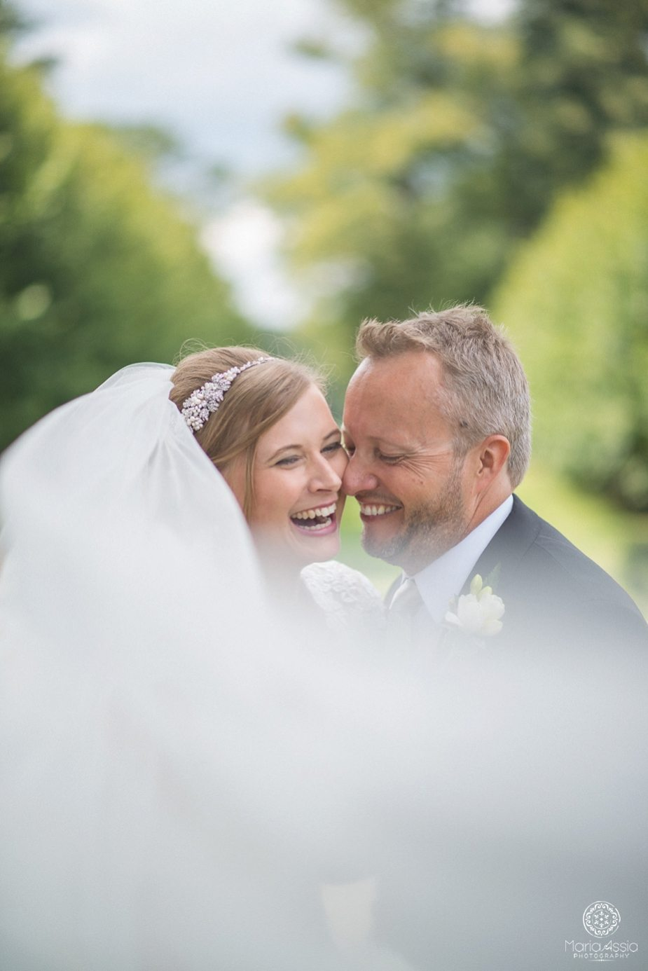 Bride and groom laughing through the veil at their Coworth Park Wildflower Meadow Wedding
