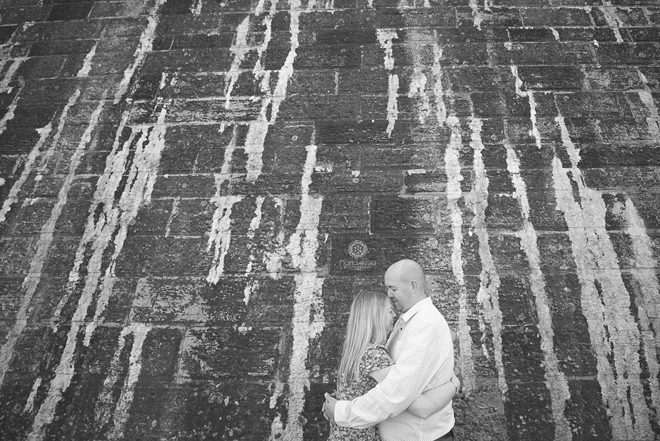 black and white photo of a man and woman hugging in front of the wall at Hurst Castle