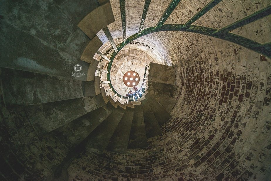 Man and woman standing at the top of a winding staircase at Hurst Castle, Creative engagement photos