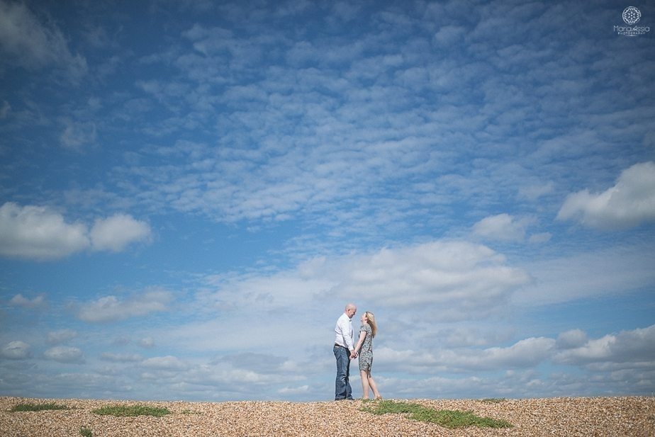 Photo of a couple holding hands on a beach with very blue sky behind them