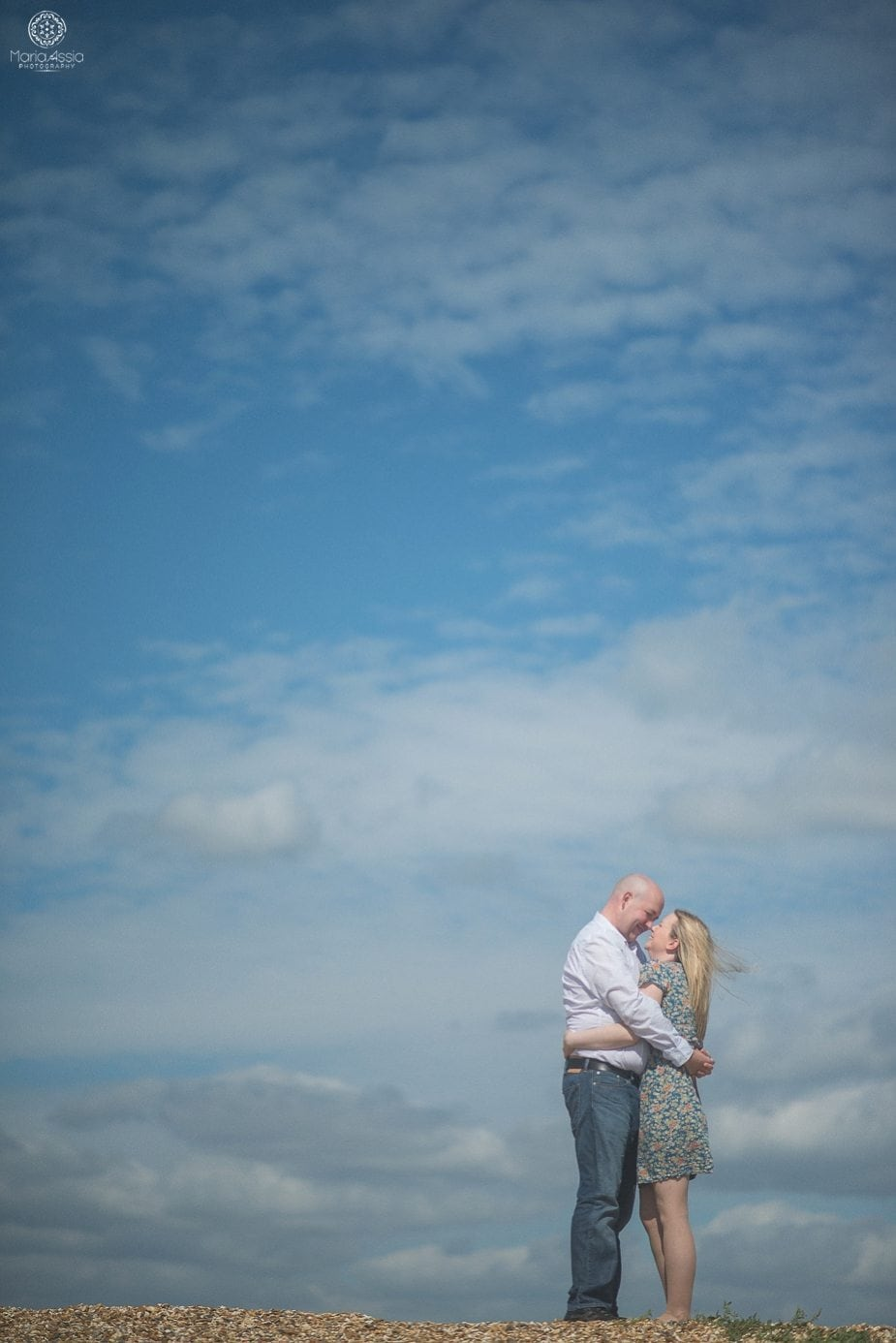 Photo of a couple hugging on a beach with very blue sky behind them
