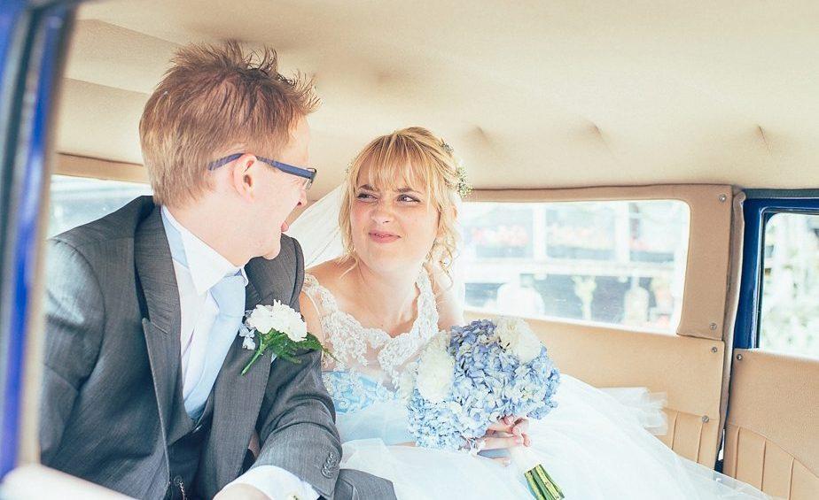 Bride smiles at her groom in their blue wedding car