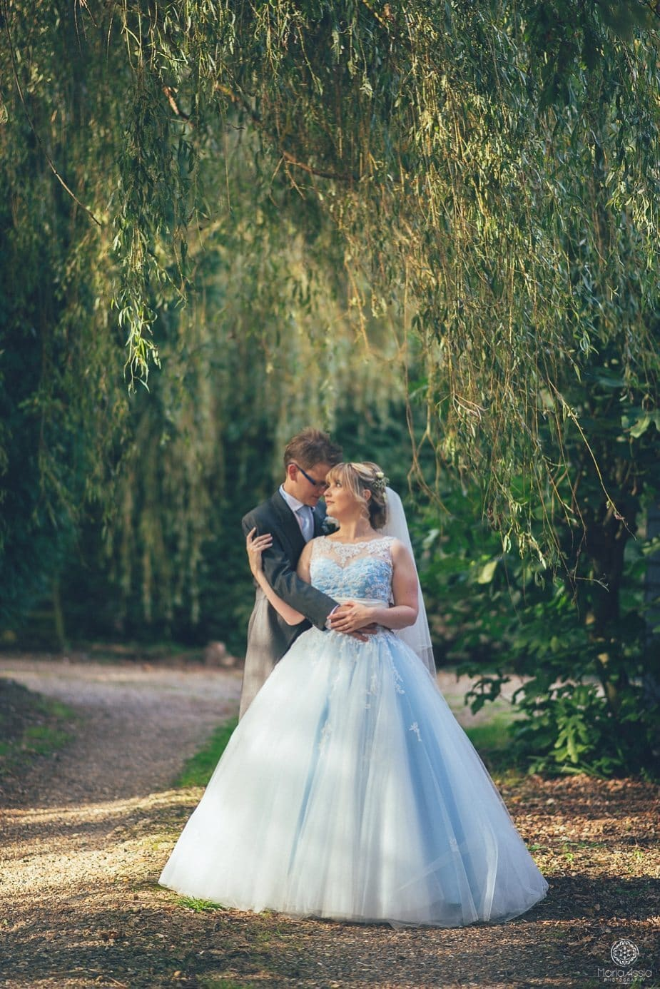 Bride and groom snuggle surrounded by sun rays and weeping willow