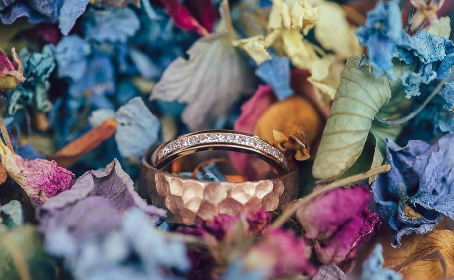 Copper wedding bands surrounded by colourful confetti