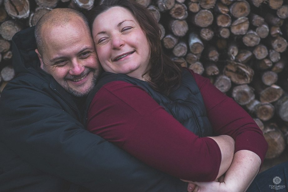 A couple hugging and laughing in front of a pile of stacked logs