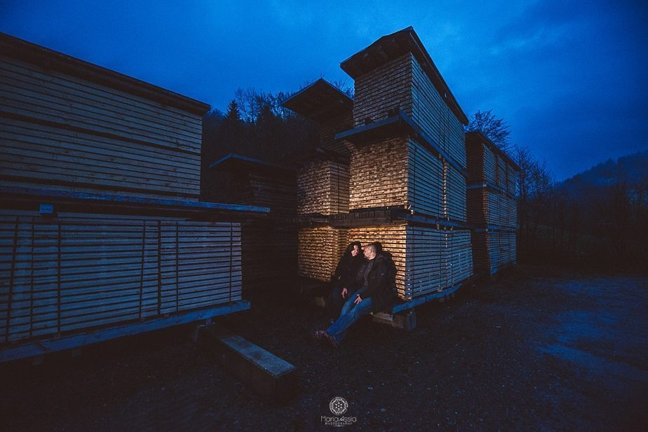 A couple leaning against stacked wooden boards on their Black Forest evening low light couple shoot captured by international wedding photographer Maria Assia Photography