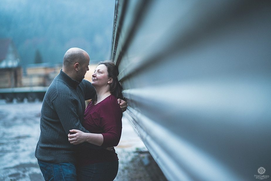 A couple smiling at each other leaning on a metal wall by international wedding photographer Maria Assia Photography