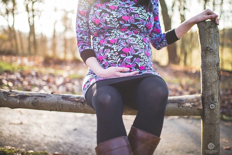 A pregnant girl holding her baby bump at Knole Park