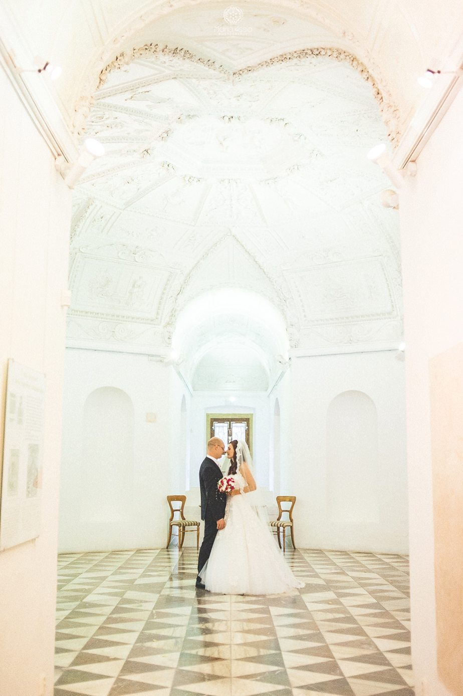 Bride and groom standing in the lobby of the Letohrádek Hvězda Prague star summer palace wedding by international weding photographer Maria Assia Photography.jpg