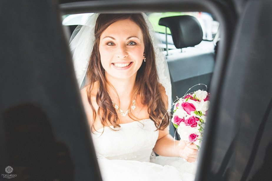 Bride smiling from the inside of her wedding car on her way to her Prague Star Summer Palace Wedding.jpg
