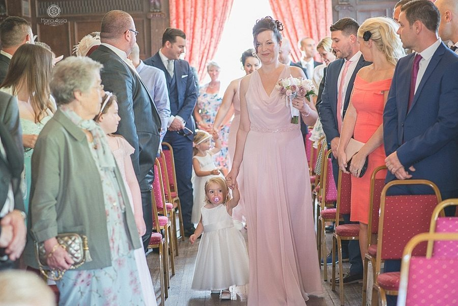 Bridesmaid walking down the aisle with a flower girl