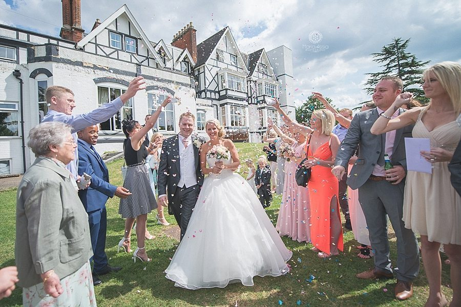 Bride and groom walking through confetti at Bickley Manor Hotel captured by Maria Assia Photographer, a Wedding photographer in Kent