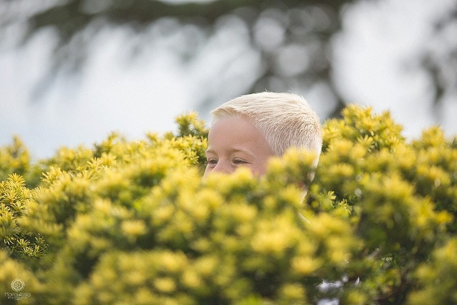 Groom's son face poking out of a bush