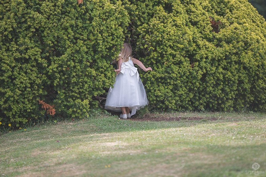 Flower girl playing hide and seek in a bush at Bickley Manor Hotel