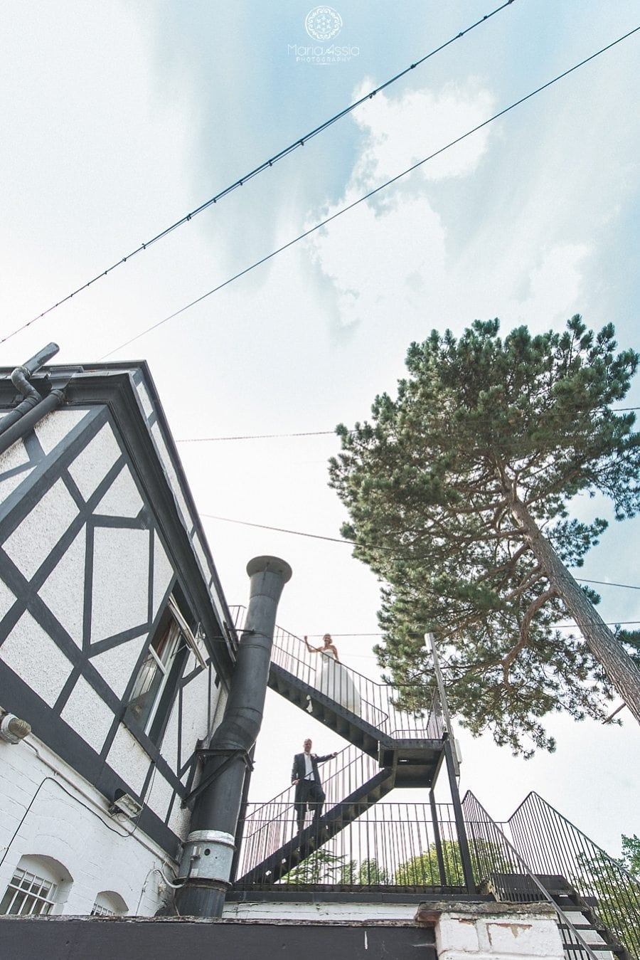 Bride and groom standing at the fire escape stairs at the Bickley Manor Hotel, captured by Wedding photographer in Kent