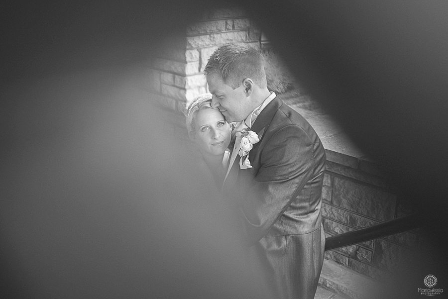 Bride and groom hugging, photographed through a gap in the fence by wedding photographer in Kent