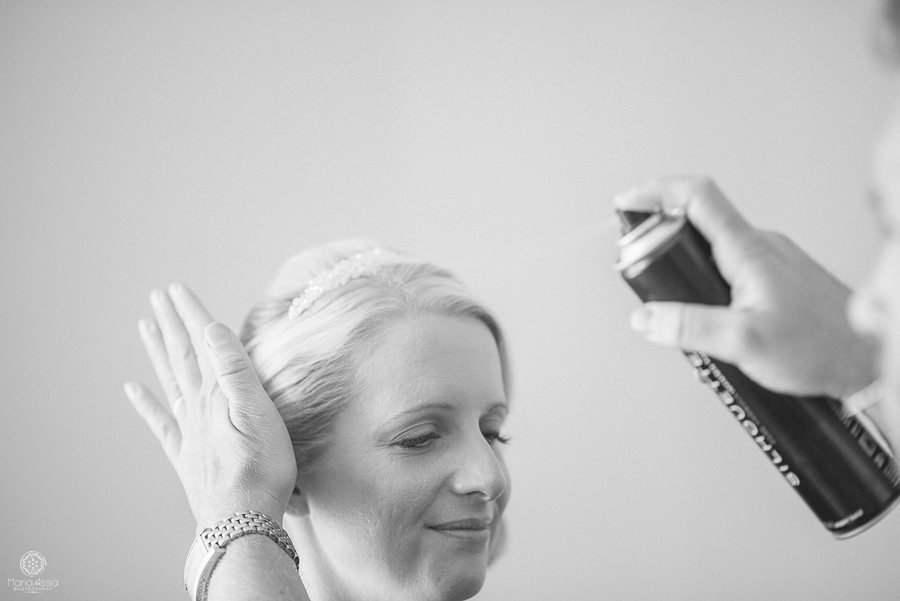 The hands of the hair stylist apply the finishing touches to the bride's hair