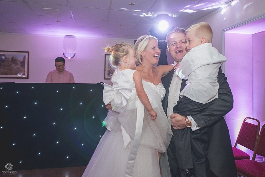 Bride and groom holding their children for their first wedding dance