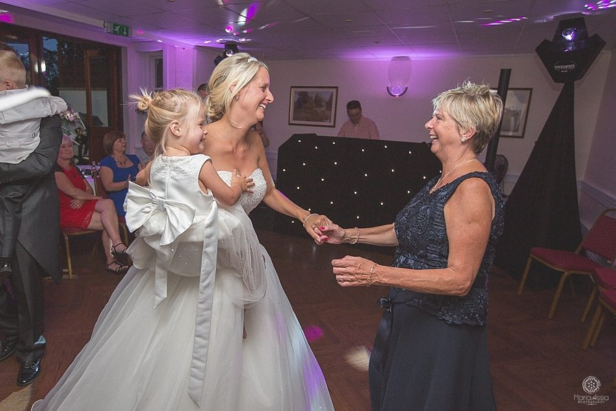 Bride dancing with her mother and daughter