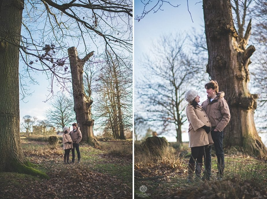Expectant couple standing under a tree in Knole Park on their Sevenoaks Knole Park winter baby bump shoot