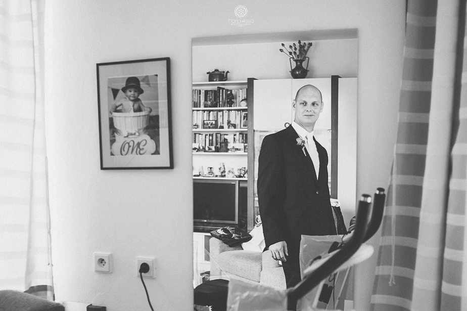 Groom looking at himself in the mirror before his Prague Star Summer Palace Wedding.jpg