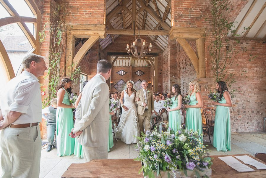 Bridesmaids in mint and lavender dresses watch the bride walking down the aisle at Shustoke Barn
